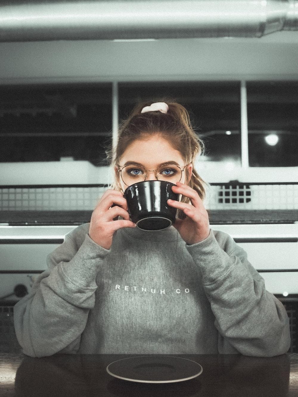 woman wearing glasses holding black ceramic mug