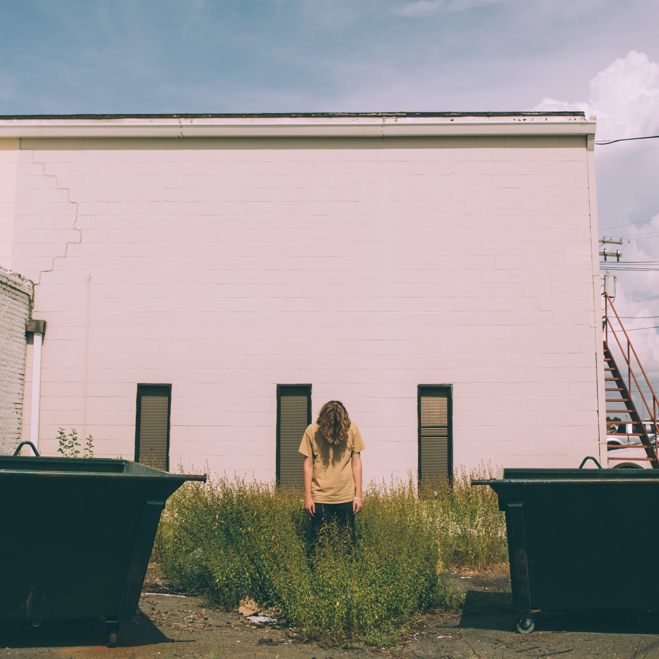 person standing near white concrete building during daytime