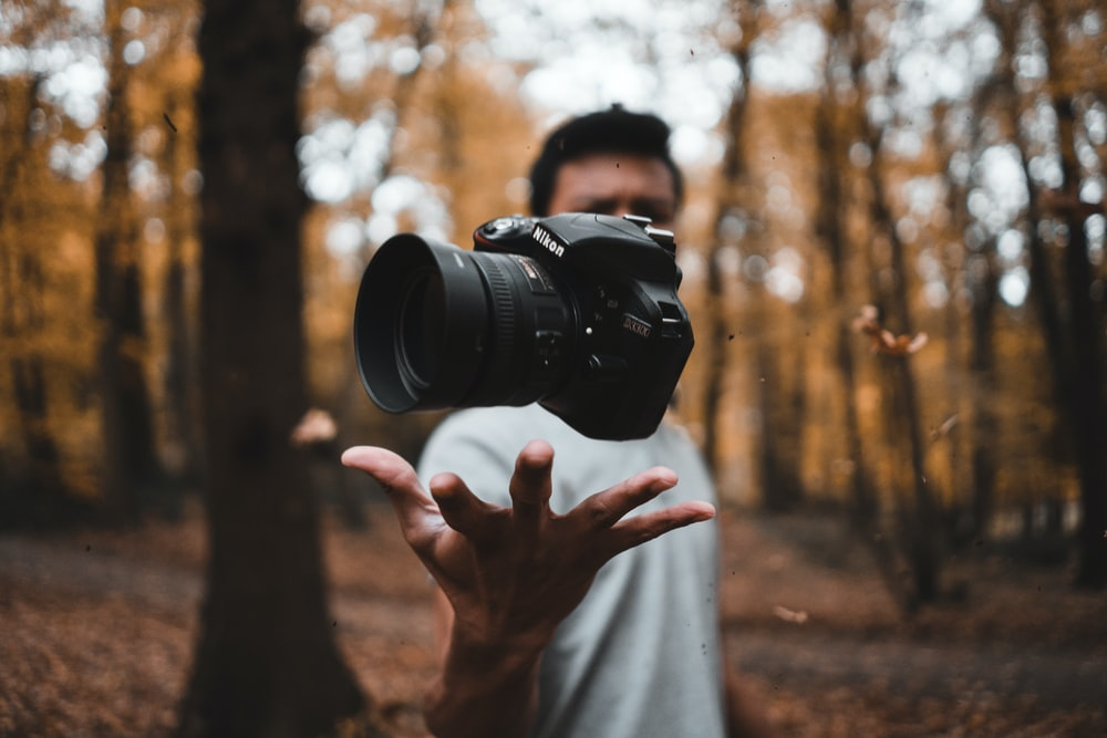 black DSLR camera floating over man's hand at the woods