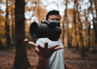 black DSLR camera floating over man's hand at the woods