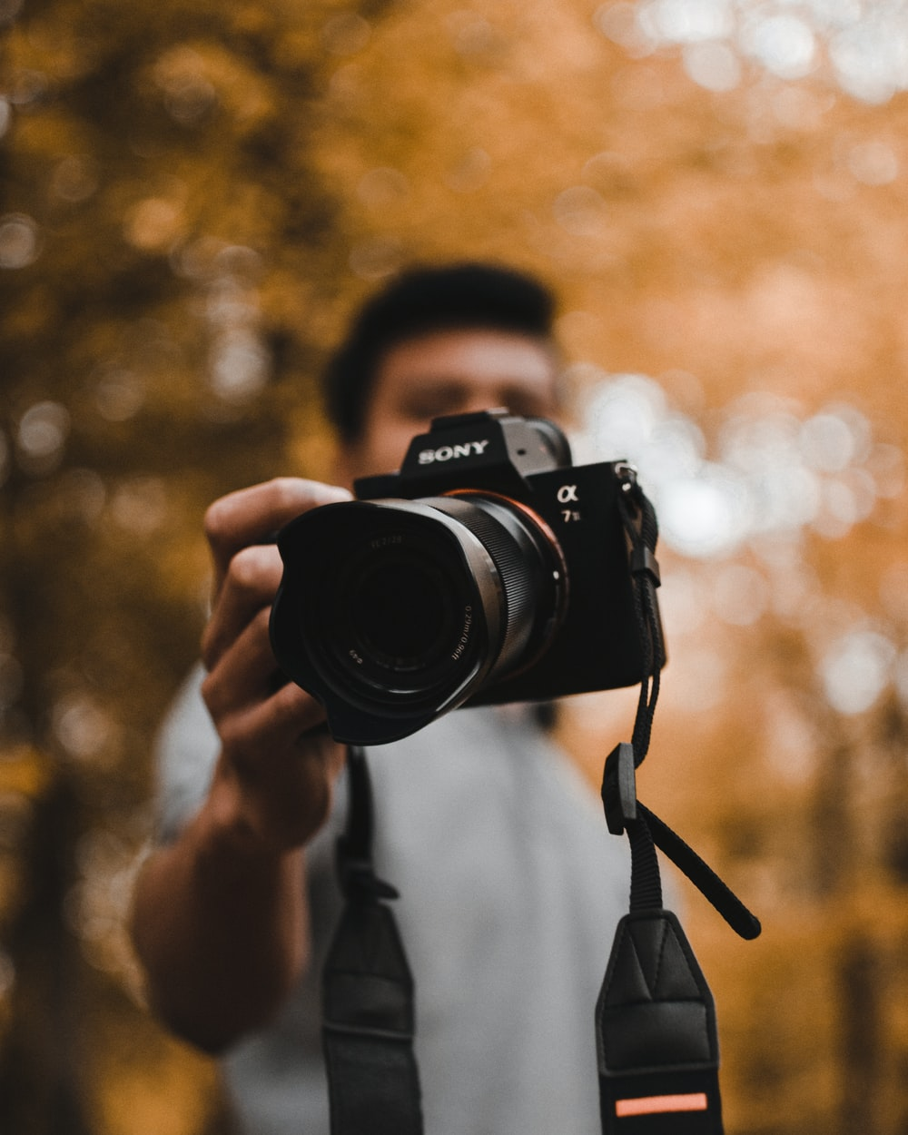 man holding Sony DSLR camera during daytime