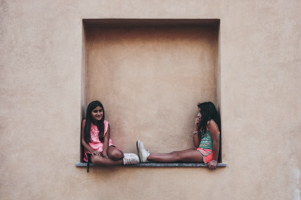 two girl in pink and green shirts sitting on wall shelf