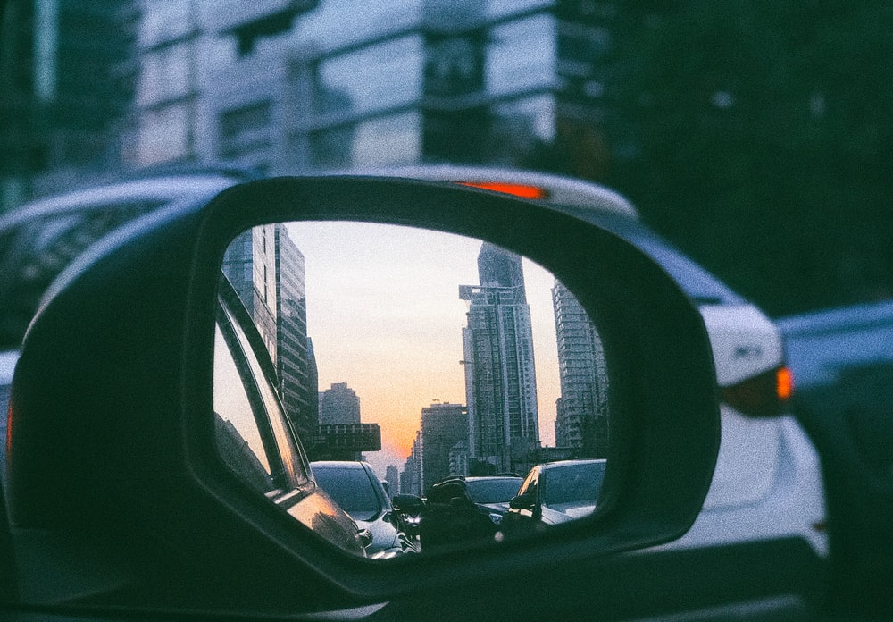 view of buildings reflected on side mirror