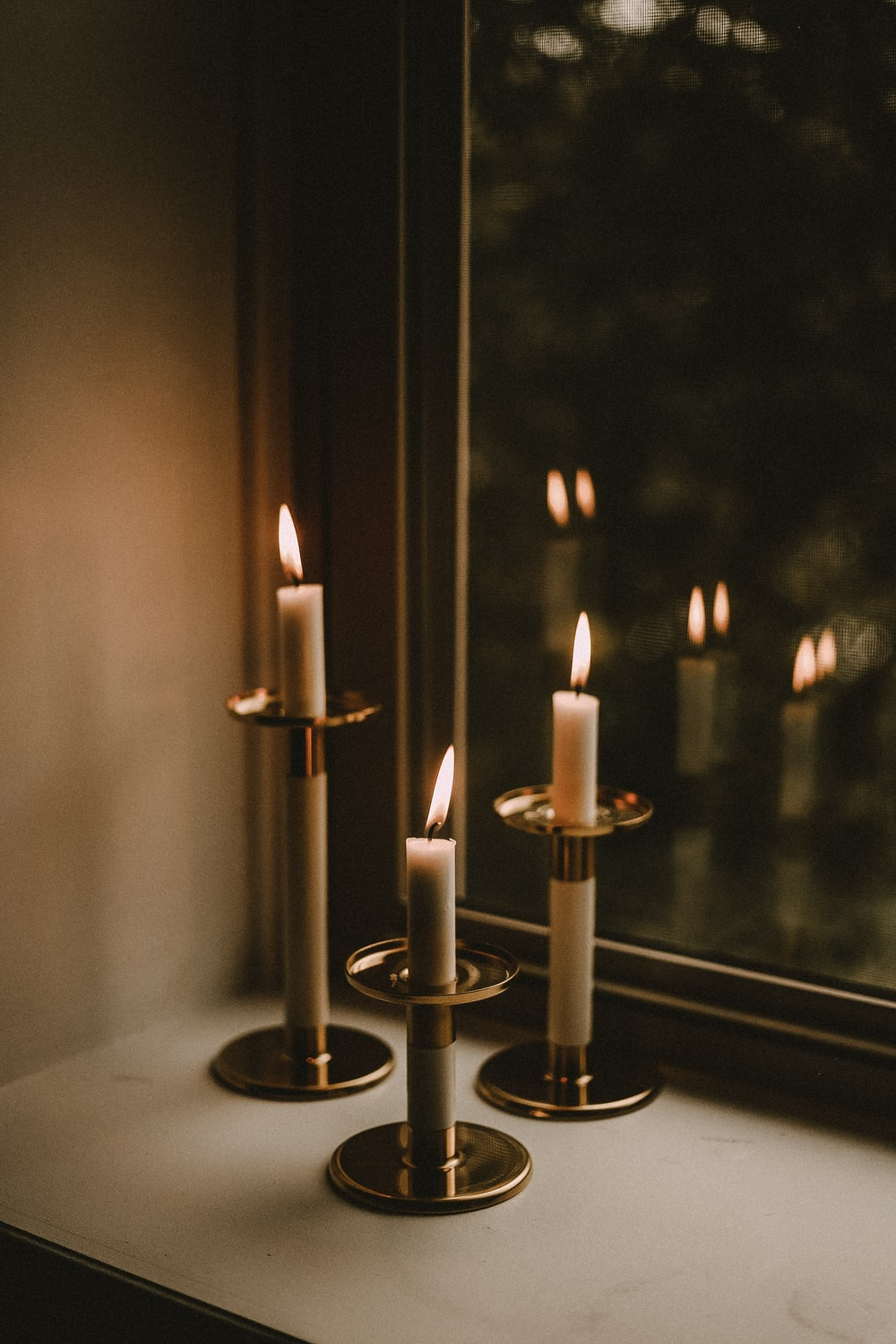 three lighten white taper candles beside window panel