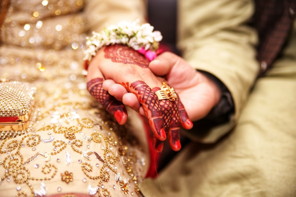 person holding hands wearing gold-colored ring