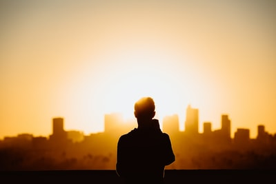 silhouette photography of standing person during sunset