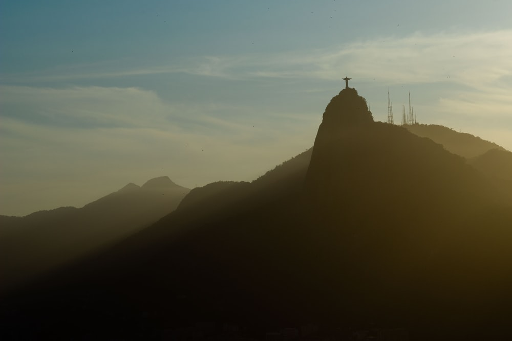 silhouette of cross on top of mountain at daytime
