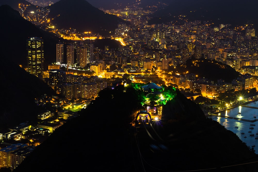 high angle photography of buildings and mountain during nighttime