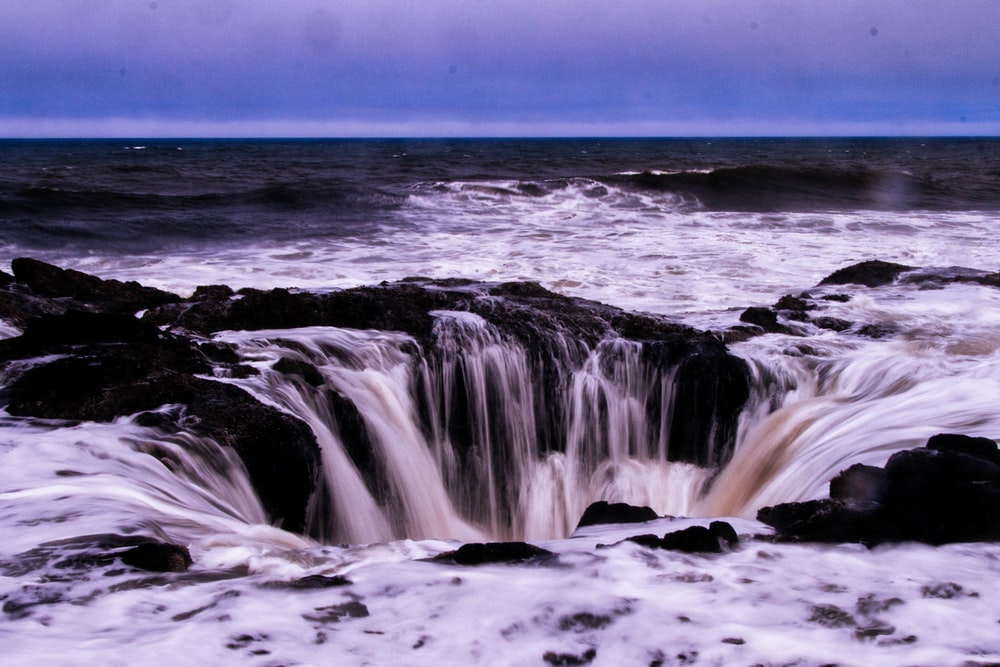 sea water falling into rocky hole at the beach