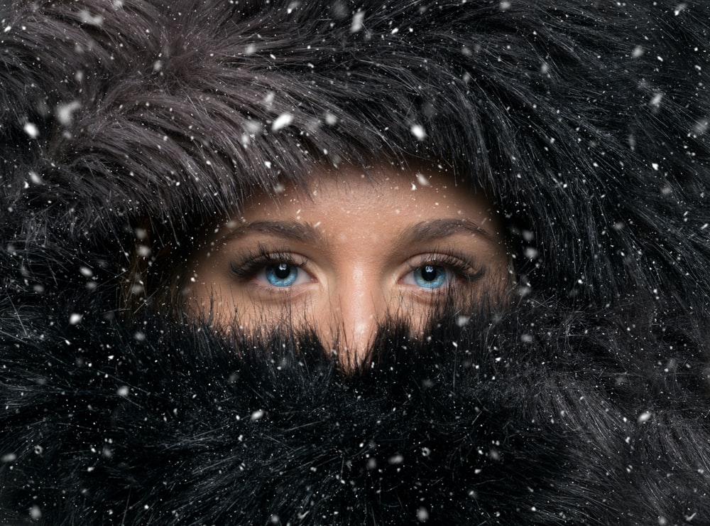 woman covered with black furred headscarf during winter