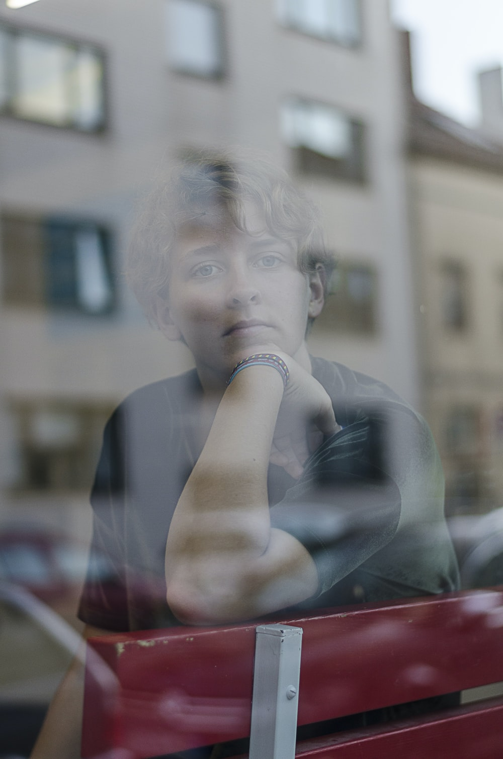 man sitting beside glass window
