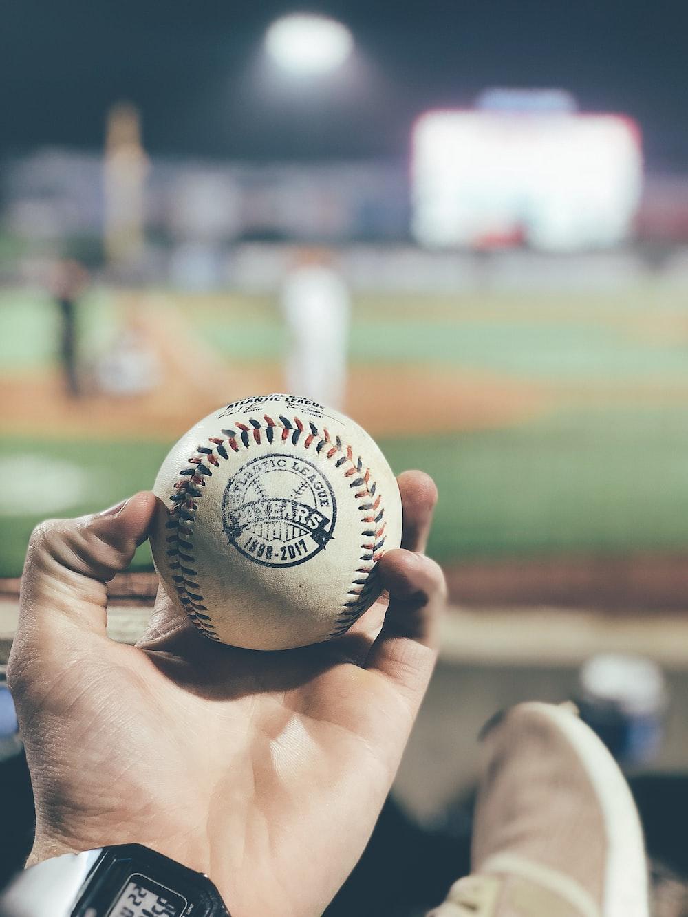 person holding white baseball