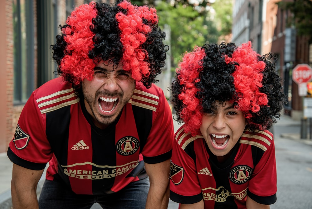 man and boy wearing black and red curl wig and smiling