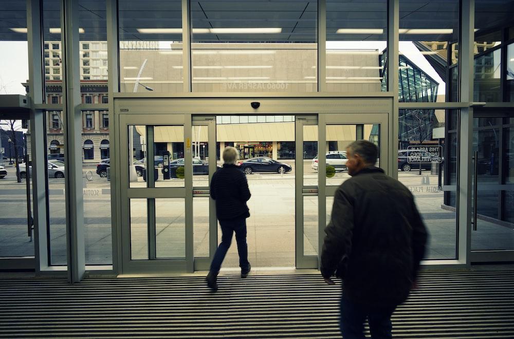 man walking front of glass door