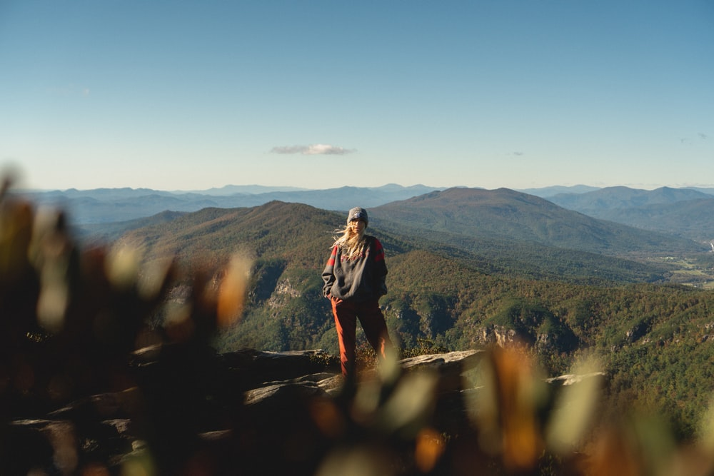 woman standing on cliff overview of mountain in landscape photography