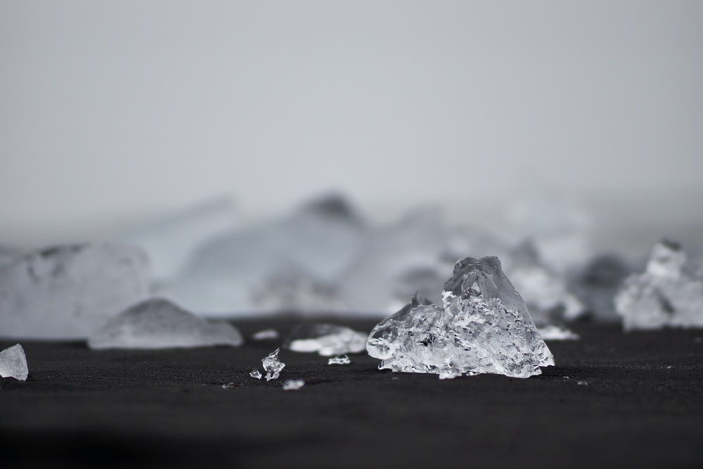 closeup photography of ice on black surface