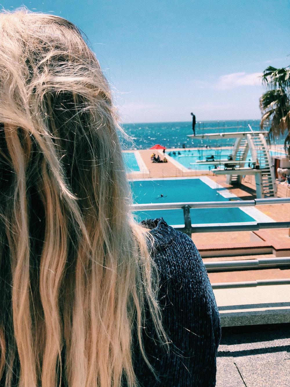 woman facing swimming pool near sea during daytime