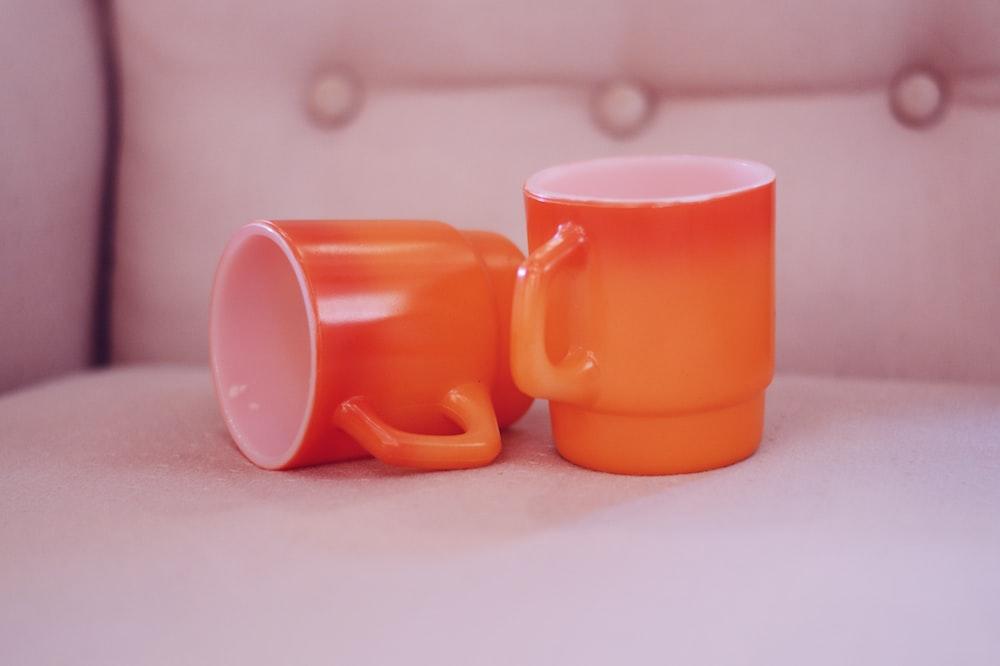 two empty orange-and-white mugs