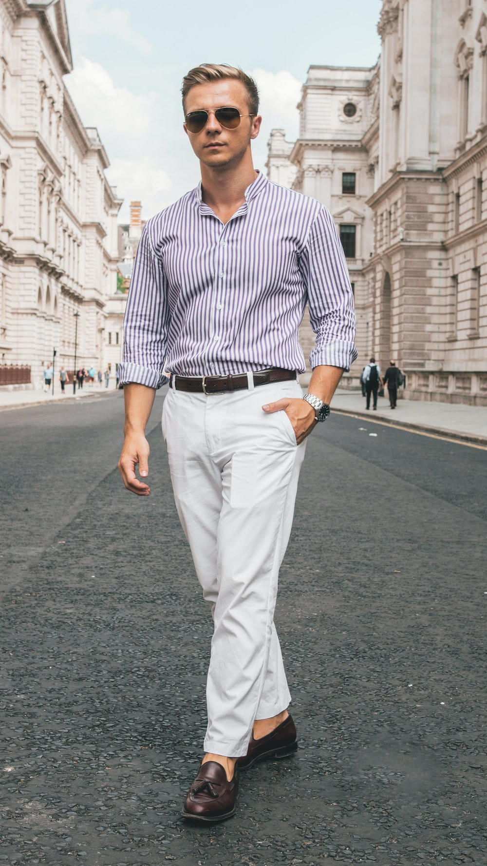 man in dress shirt and white denim jeans standing on road during daytime