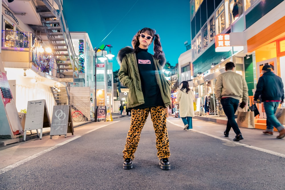 woman in green jacket stands and pose on street