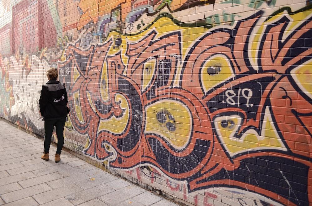 woman walking beside graffiti during daytime