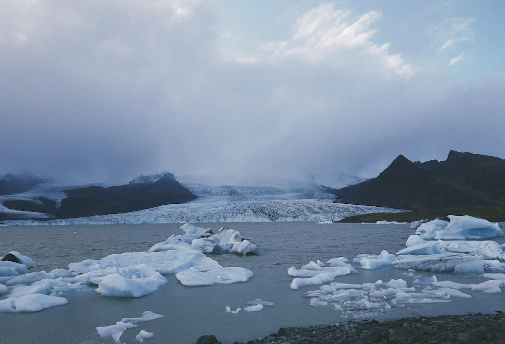 ice berg on water under white sky