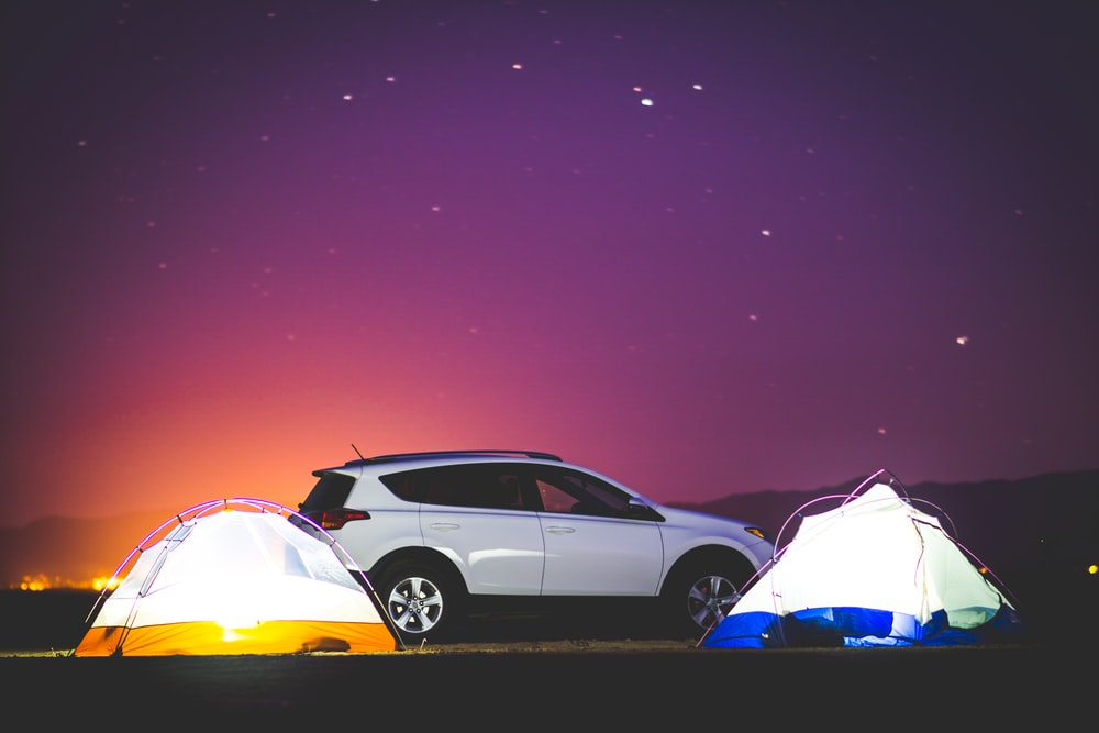 white SUV in between dome tents under starry night