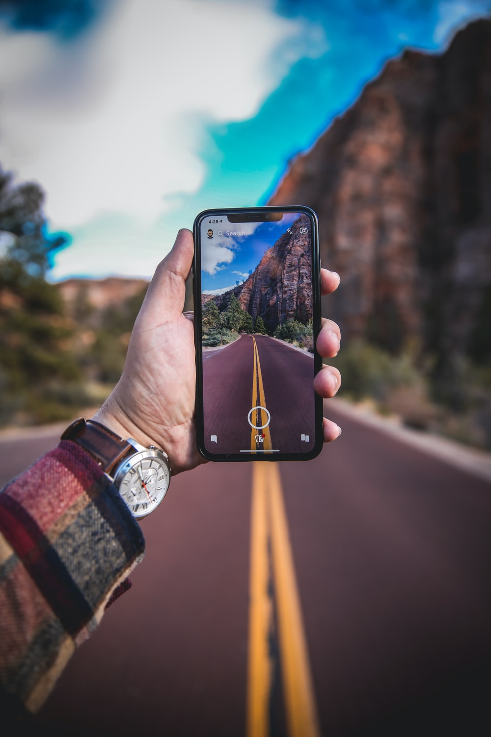 person holding smartphone with empty road photo
