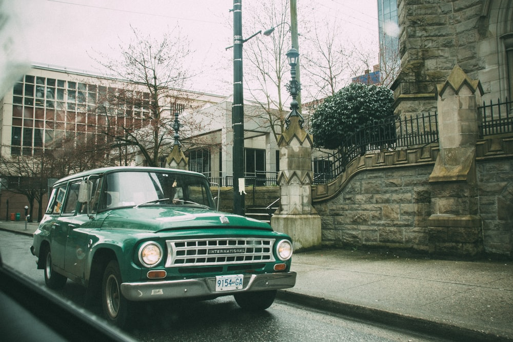 classic green station wagon on road during daytime