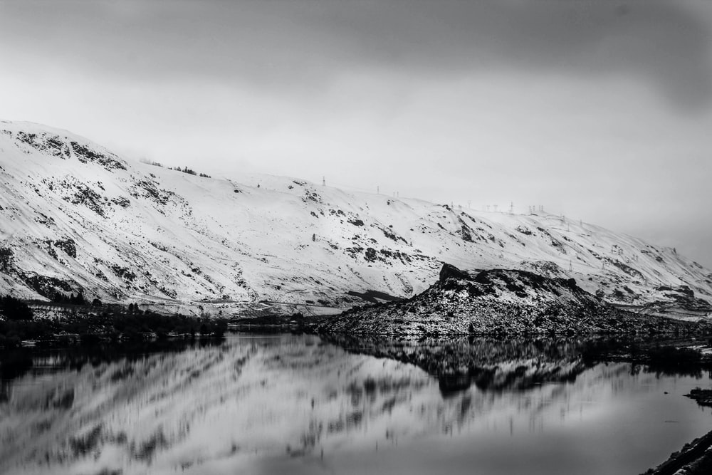 grayscale nature photography of body of water beside snow capped mountain under cloudy sky