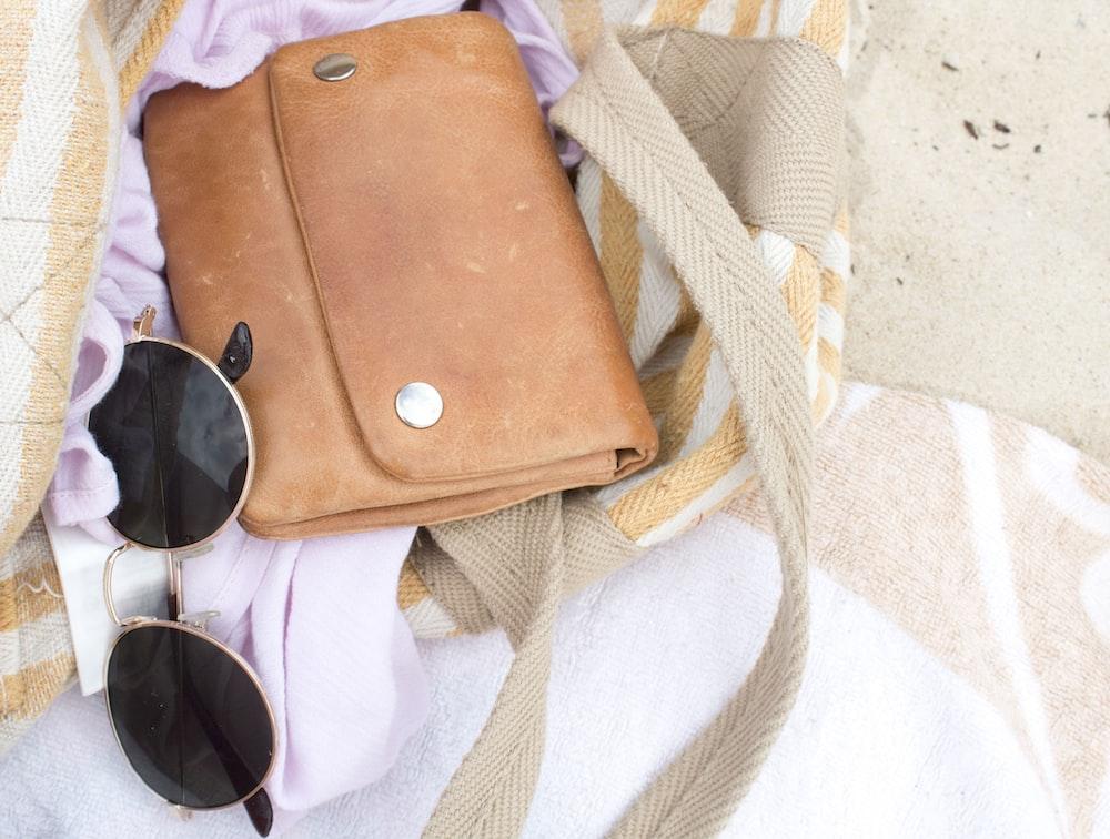 brown leather shoulder bag with dark sunglasses