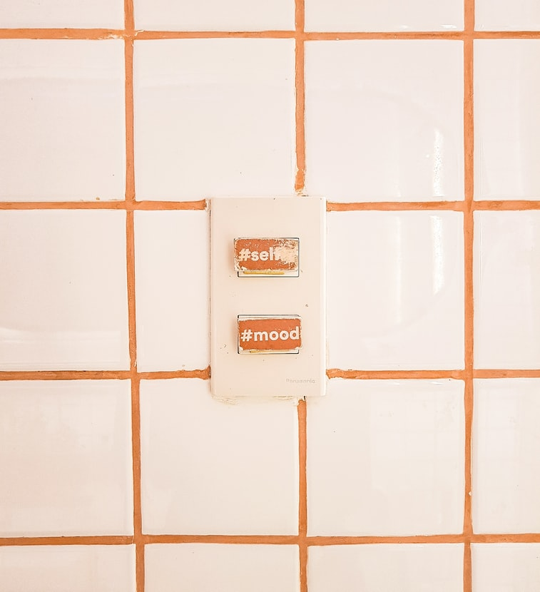 A photo of a wall with an electrical outlet on it. The two ports for the outlet are covered with orange stickers. The top one says #self and the bottom says #mood. The wall has an orange grid painted on it, like it's graph paper.