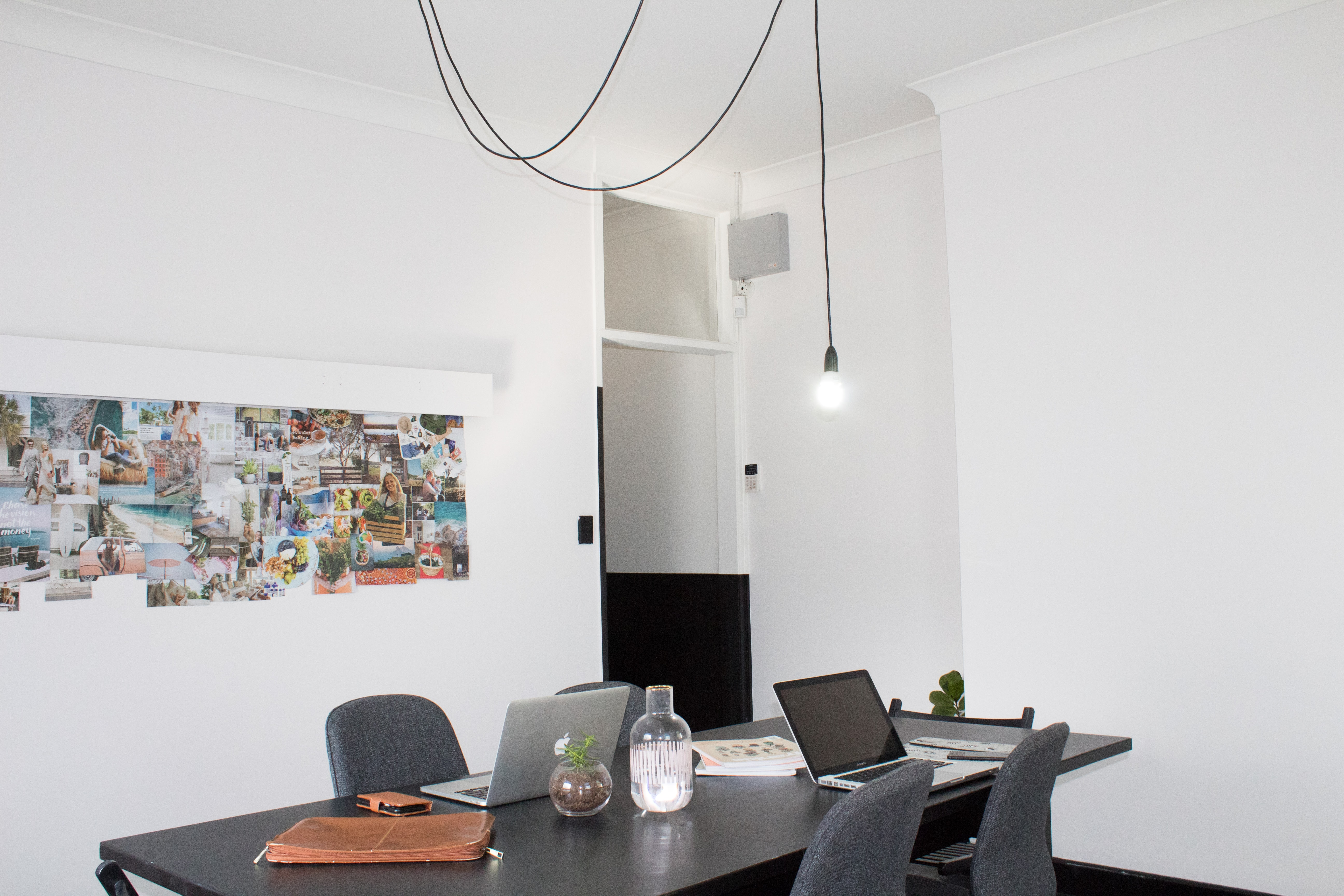 rectangular black wooden desk in white painted wall room