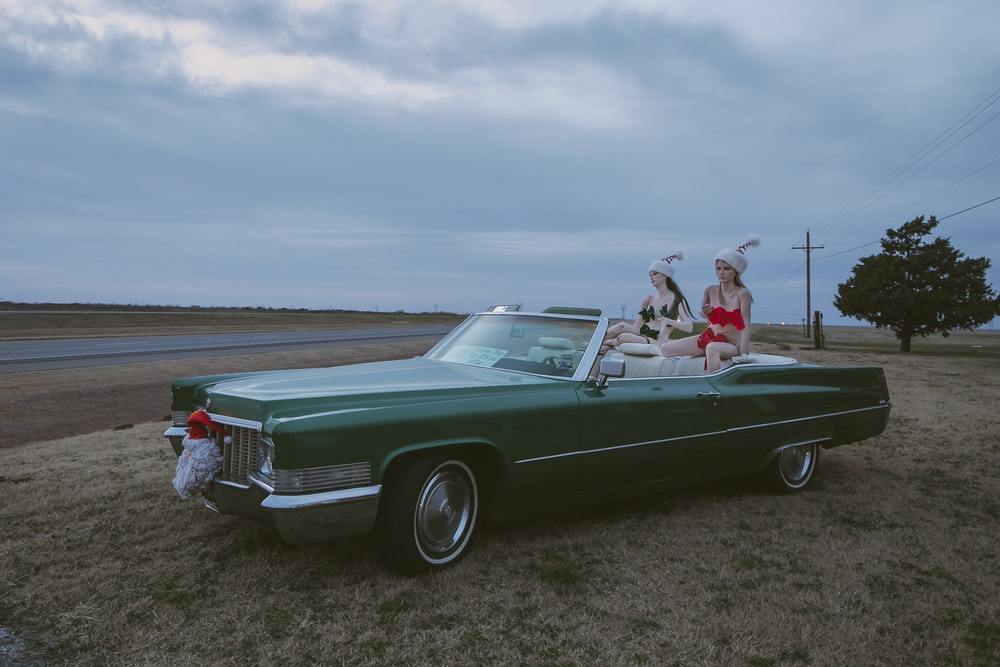 two women in classic convertible car