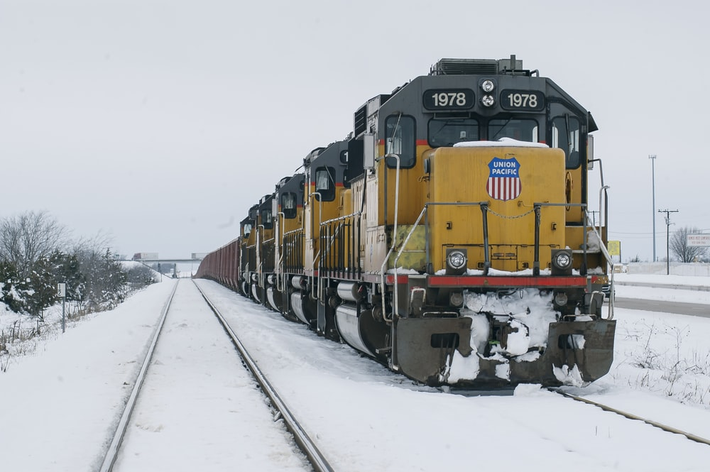 yellow and black 1978 train surrounded by snow