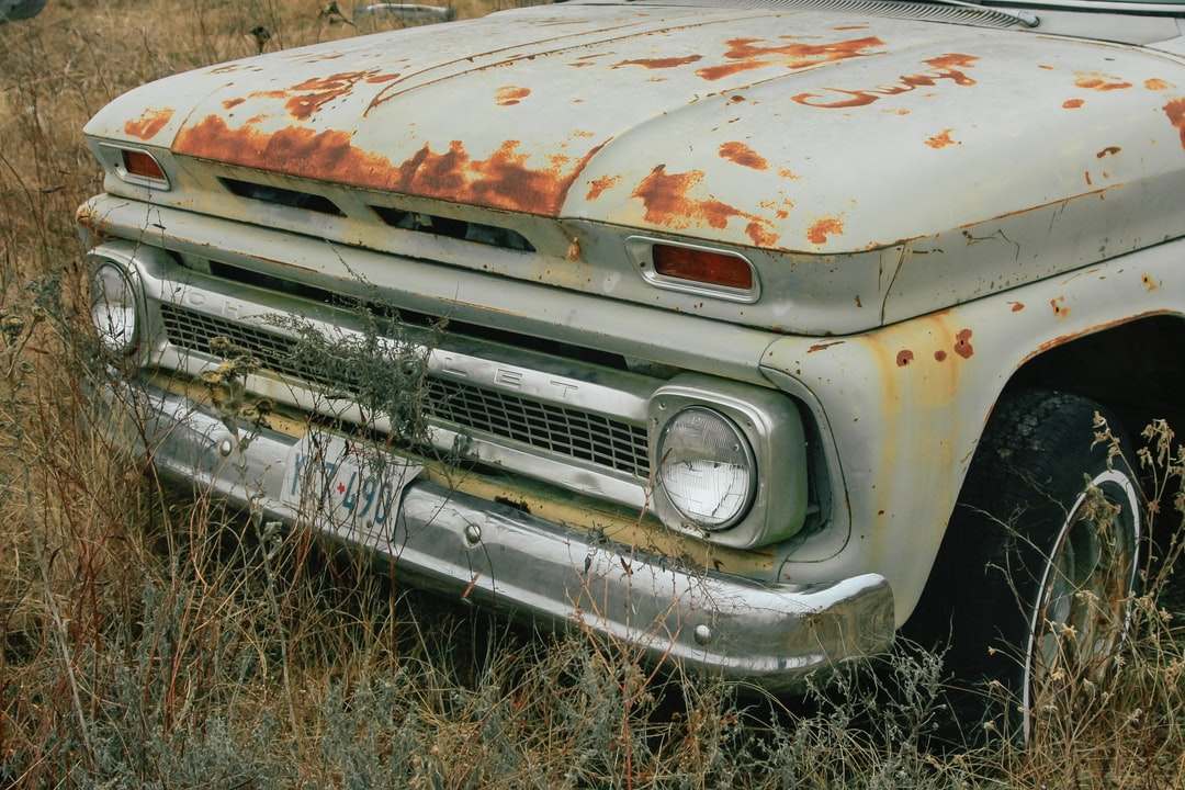 An old rusty classic truck abandoned in a field