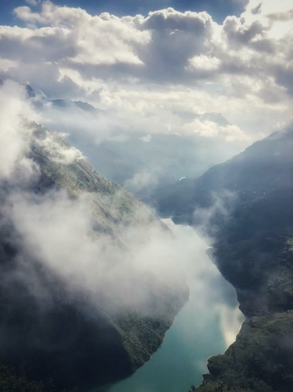 river beside mountains under grey clouds