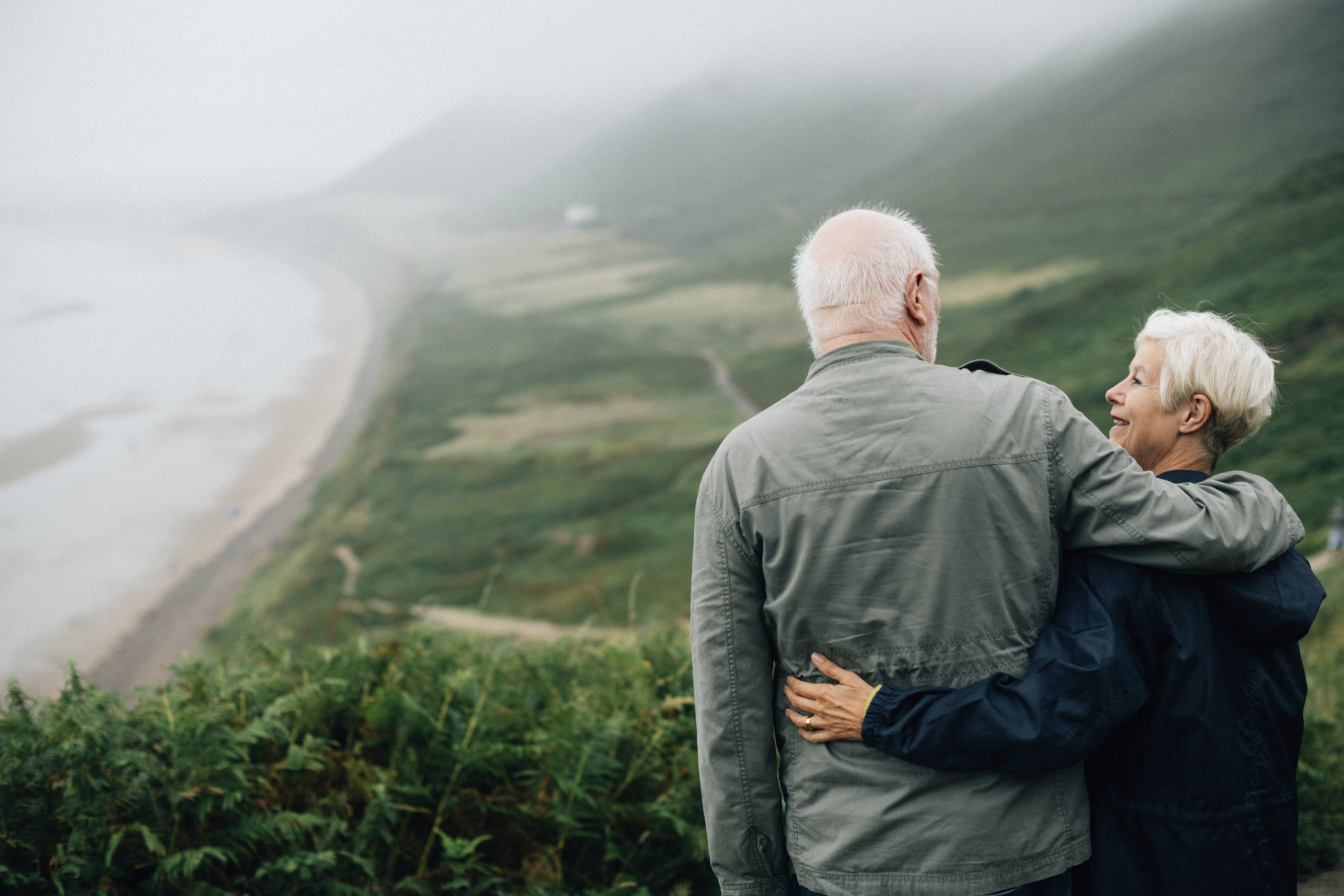 man and woman looking to each other on cliff