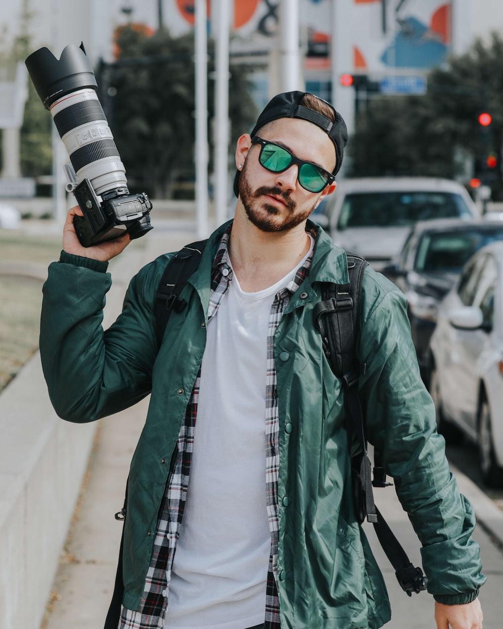 man holding DSLR camera wearing green button-up jacket beside cars
