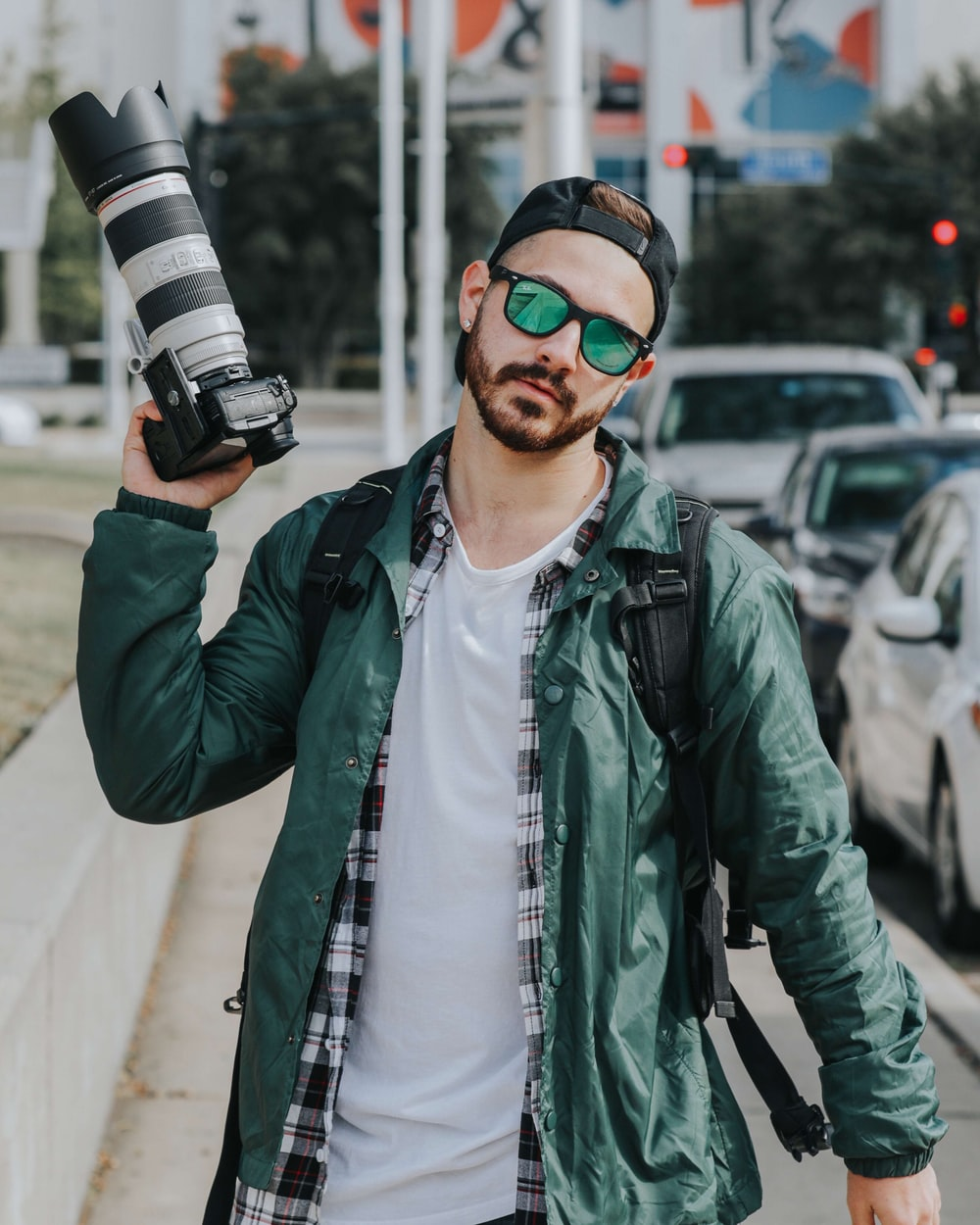 man holding DSLR camera wearing green button-up jacket beside cars