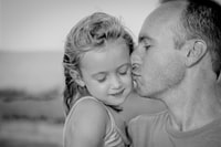 boy kissing her daughter