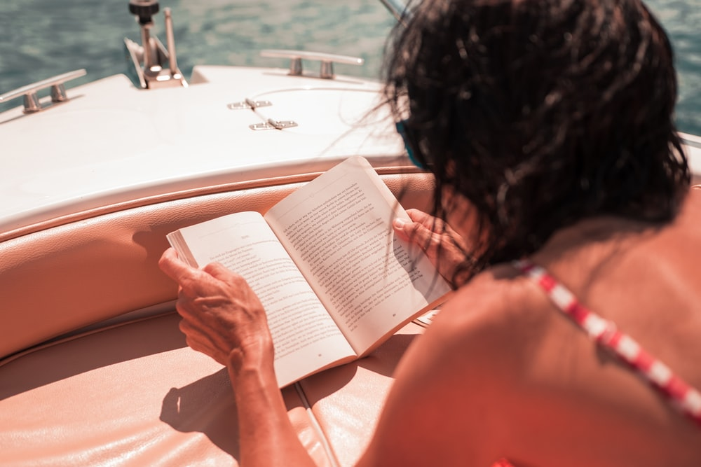 woman riding boat reading book