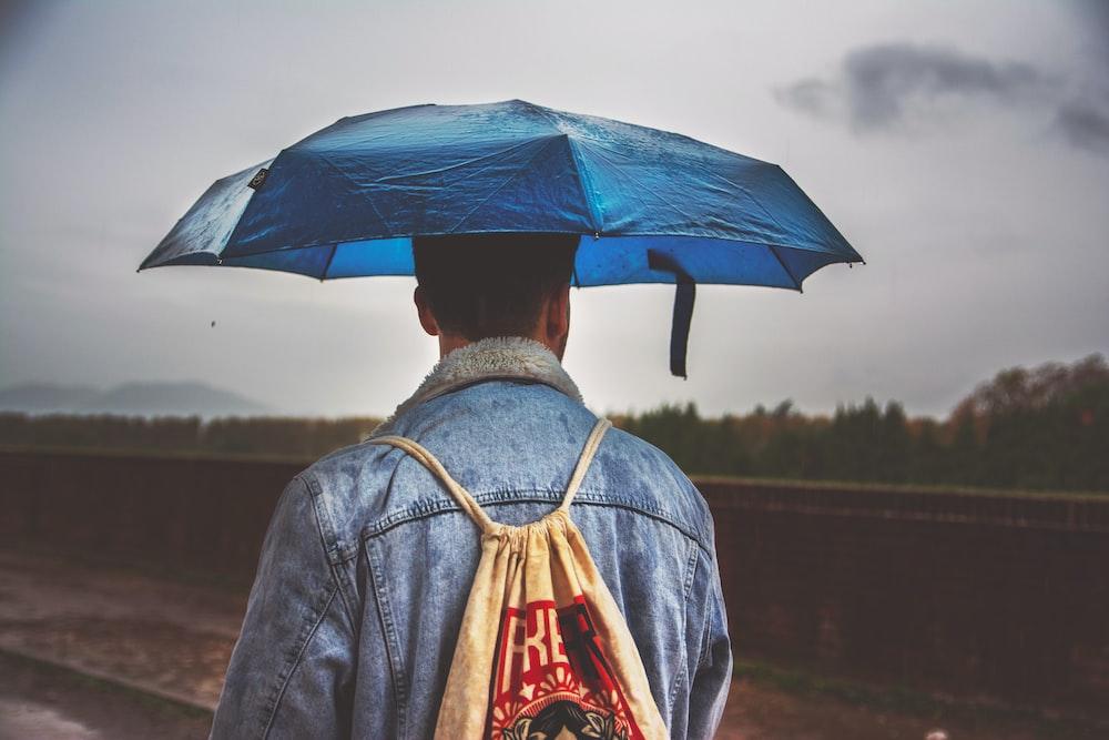 man under blue umbrella with brown drawstring bag