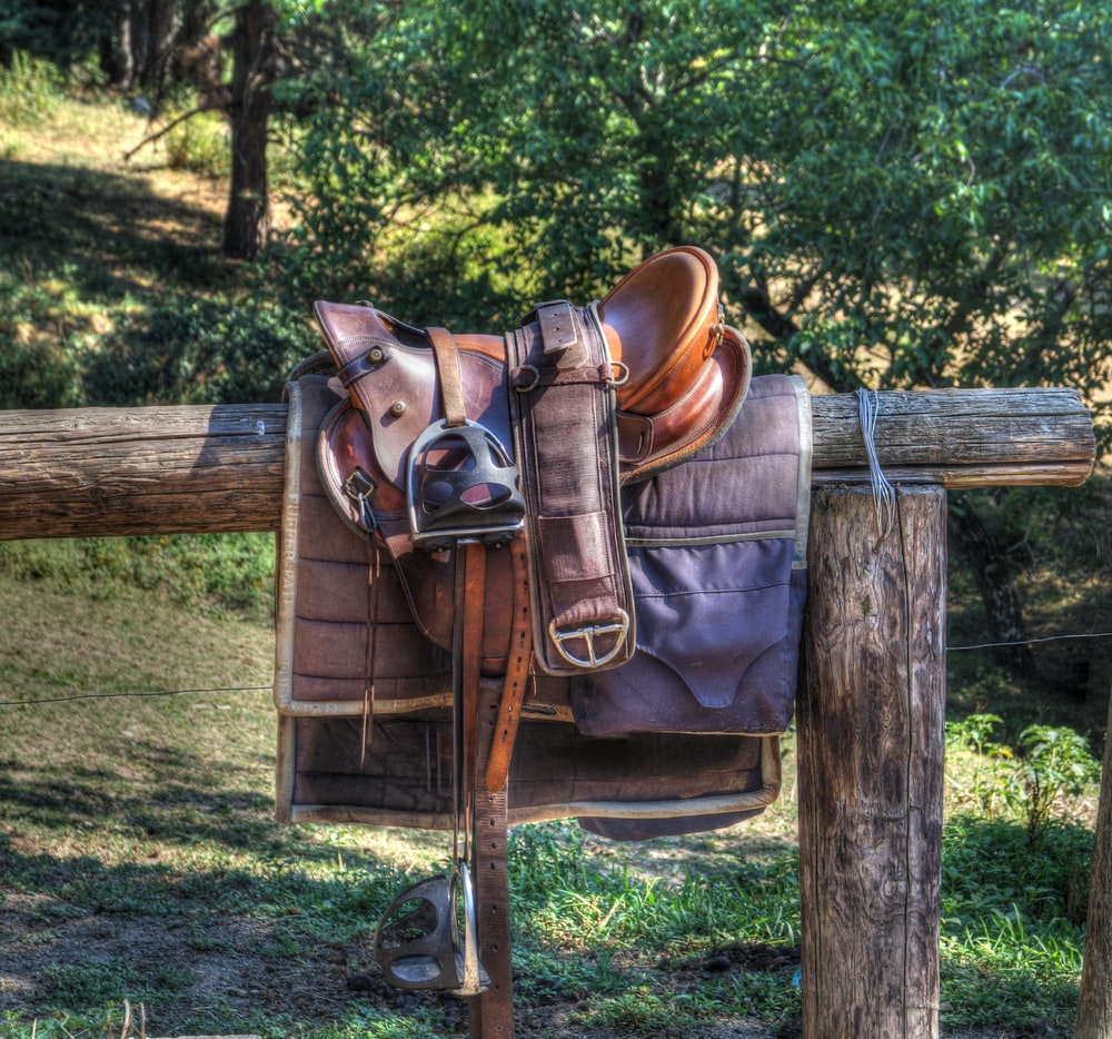 brown leather horse saddle on fence