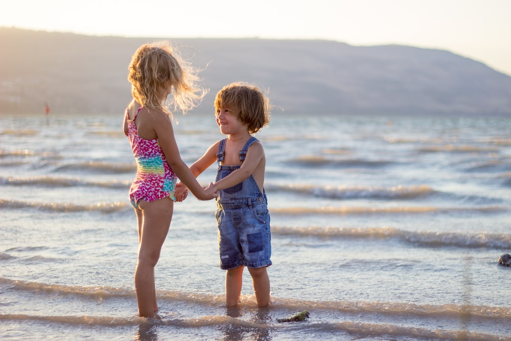 two girls standing on seashore
