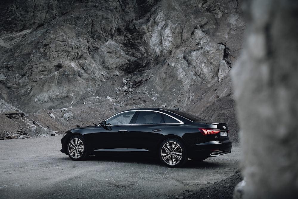 black sedan parked near gray rock formation
