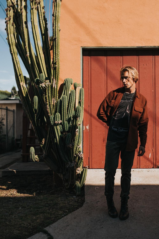 man standing beside cactus plant
