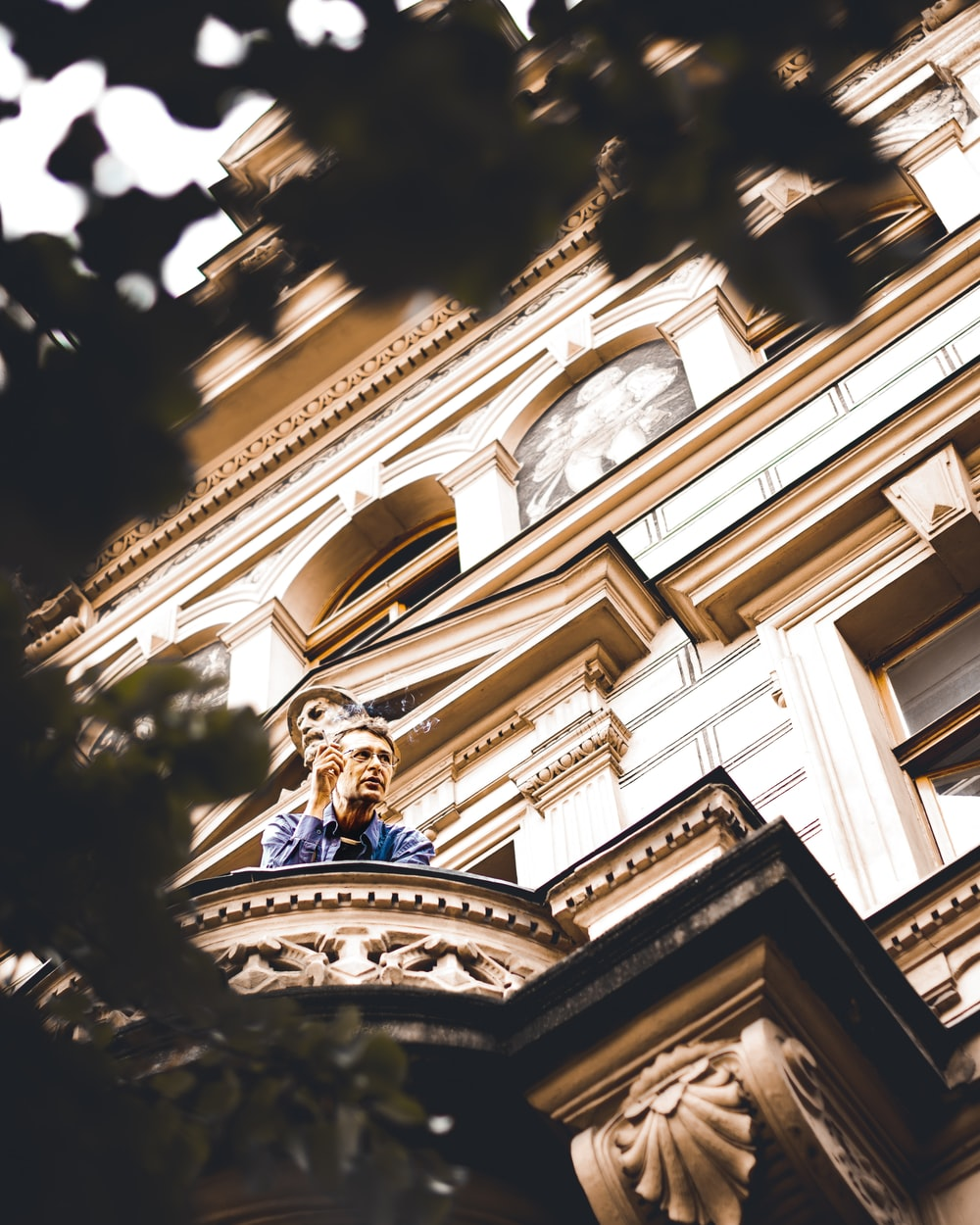 low angle photography of man leaning on balcony