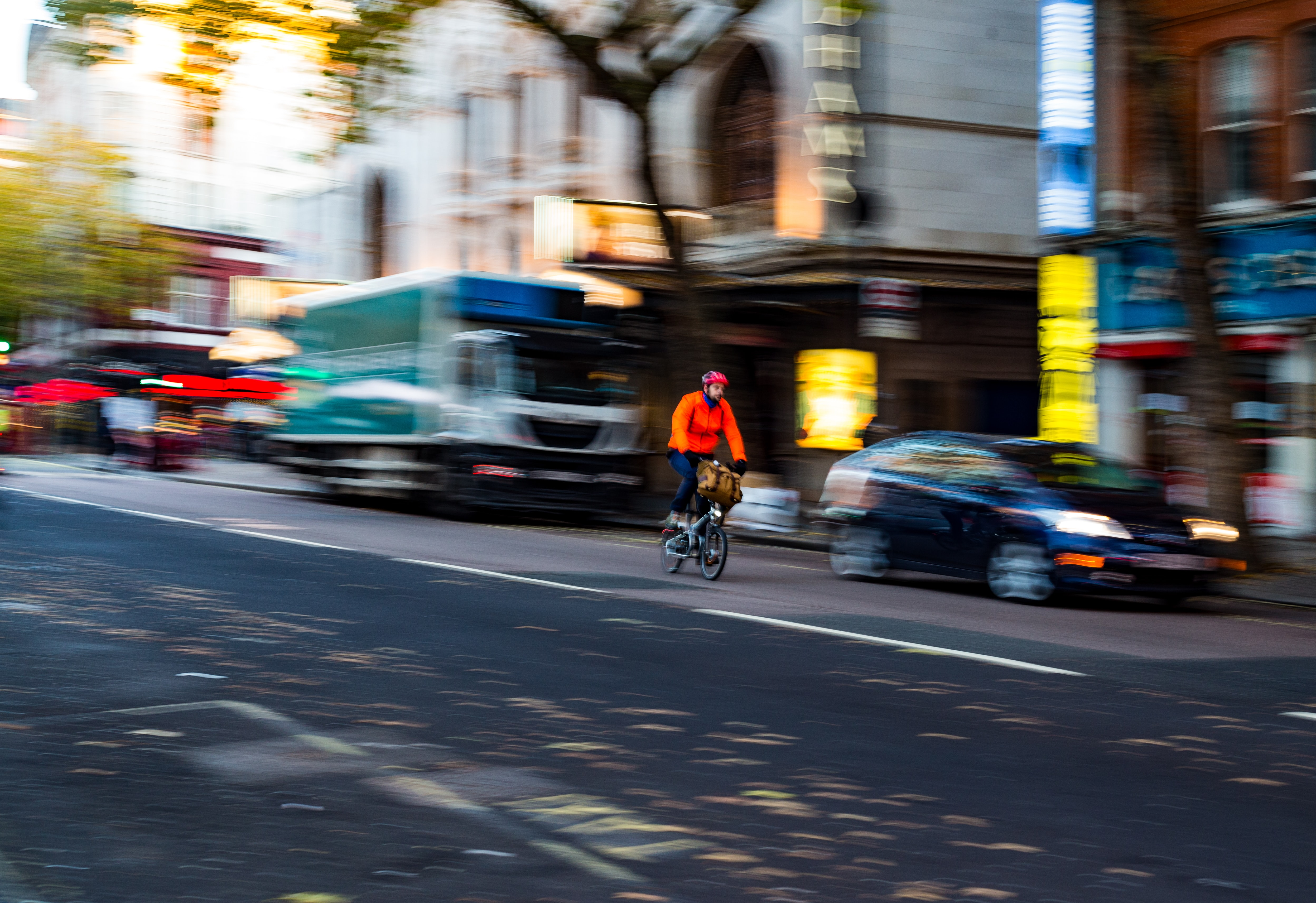 panning photography of man riding bike on road