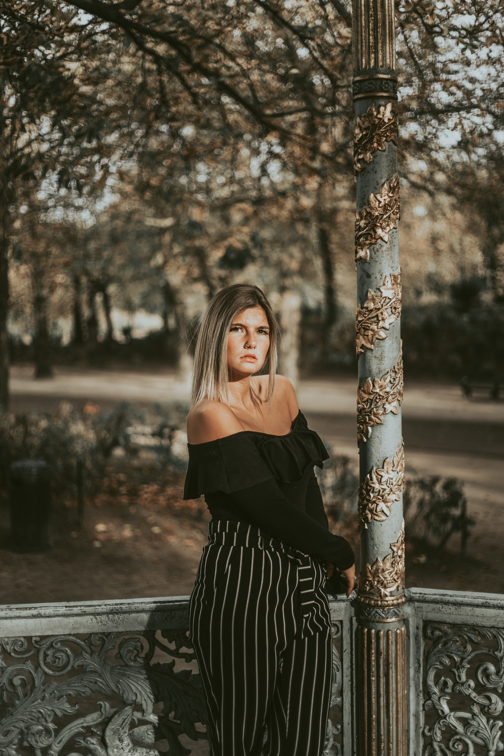 woman wearing black off-shoulder dress near trees